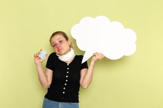 Widok z przodu młoda kobieta czuje się bardzo chora i chora, trzymając ogromny biały znak trzymający pigułki na jasnozielonej ścianie lekarskiej choroby zdrowia