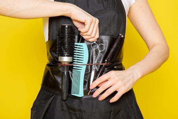 Widok z przodu młoda kobieta fryzjerka w białej pelerynie z czarnym t-shirtem, biorąc nożyczki ze szczotkami falować włosy
