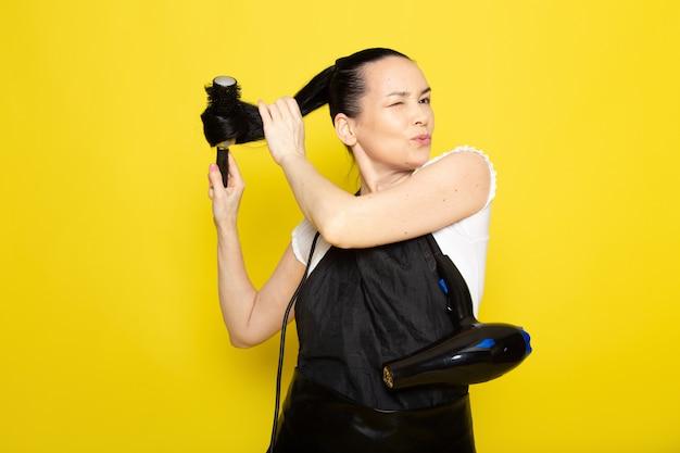 Widok z przodu młoda kobieta fryzjerka w białej pelerynie z czarnym t-shirtem, szczotkując włosy, uśmiechając się, stwarzając