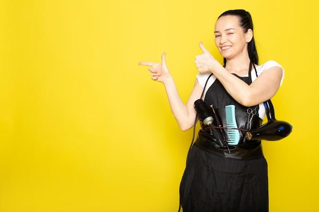 Widok z przodu młoda kobieta fryzjerka w białej pelerynie z czarnym t-shirtem ze szczotkami i suszarką do włosów, uśmiechając się, witając pozowanie