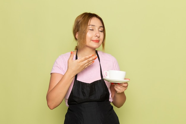 Widok z przodu młoda kobieta fryzjerka w różowy t-shirt i czarną pelerynę trzymając kubek uśmiechnięty na zielono