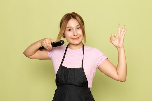 Widok z przodu młoda kobieta fryzjerka w różowy t-shirt i czarną pelerynę ustalającą włosy szczotką do włosów na zielono
