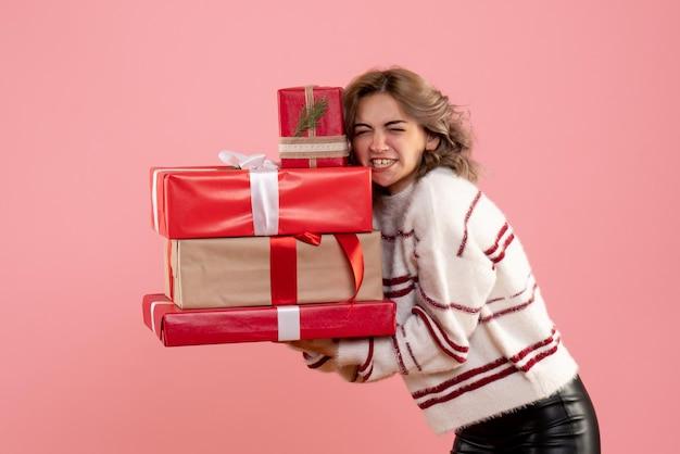 Widok z przodu młoda kobieta gospodarstwa prezenty świąteczne