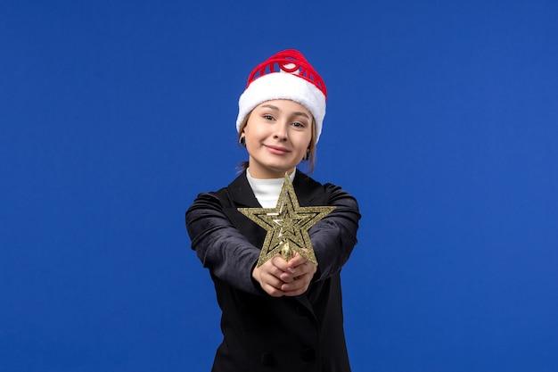 Widok z przodu młoda kobieta gospodarstwa zabawka gwiazda na niebieskim tle kolor nowego roku kobieta wakacje