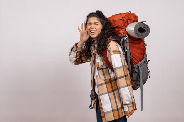 Widok z przodu młoda kobieta idzie na piesze wycieczki słuchając na białym tle kampus las góra wysokość turystyczna powietrze natura
