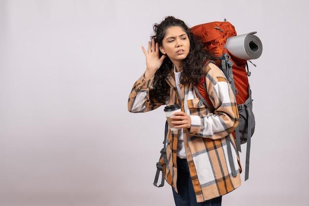 Widok z przodu młoda kobieta idzie na piesze wycieczki trzymając kawę na białym tle turystyczne wakacje kampus powietrze górska wycieczka las