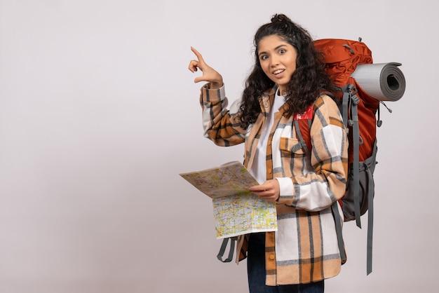 Widok z przodu młoda kobieta idzie na piesze wycieczki z mapą na białym tle wysokość kampus las góra turystyczna powietrze natura