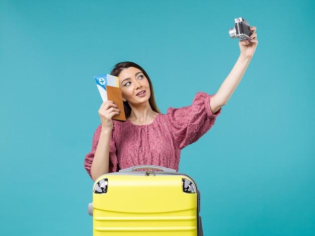 Widok z przodu młoda kobieta idzie na wakacje trzymając aparat fotograficzny na jasnoniebieskim tle podróż wakacje kobieta za granicą morze