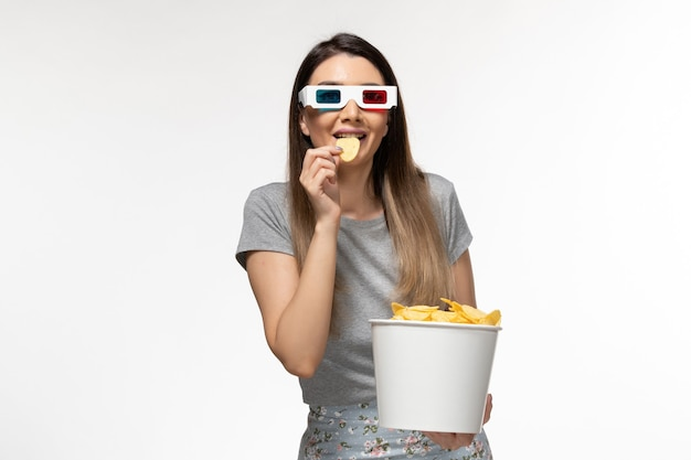 Widok z przodu młoda kobieta jedzenie cipsów podczas oglądania filmu d okulary przeciwsłoneczne na białej powierzchni