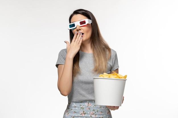 Widok z przodu młoda kobieta jedzenie cipsów podczas oglądania filmu d okulary przeciwsłoneczne na jasnobiałej powierzchni
