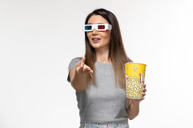 Widok z przodu młoda kobieta jedzenie popcornu i oglądanie filmu d okulary przeciwsłoneczne na jasnobiałej powierzchni