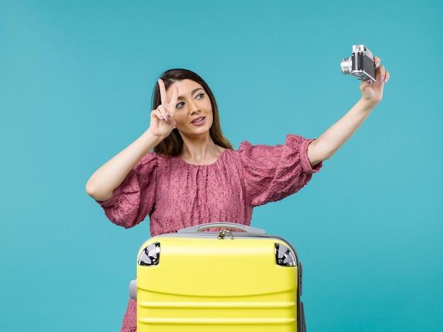 Widok z przodu młoda kobieta jedzie na wakacje i robienie zdjęć na niebieskim tle podróż kobieta za granicą wakacje morskie