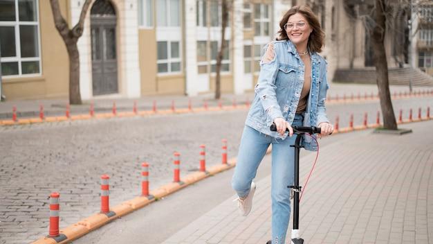Widok z przodu młoda kobieta jedzie skuterem elektrycznym