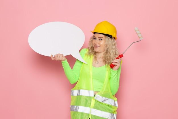 Widok z przodu młoda kobieta konstruktor w zielonym kasku kombinezonu budowlanego, trzymając biały znak i tylko uśmiechając się na różowych pracach budowlanych architektury przestrzeni