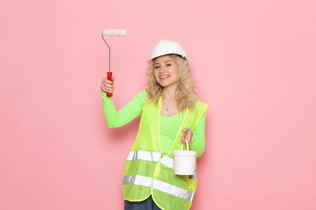 Widok z przodu młoda kobieta konstruktor w zielonym kombinezonie budowlanym biały kask gospodarstwa farby może na różowym miejscu pracy architektury pracy budowlanej