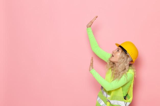 Widok z przodu młoda kobieta konstruktor w zielonym kombinezonie budowlanym żółty kask tylko pozuje przestraszony na różowej pracy budowlanej architektury kosmicznej