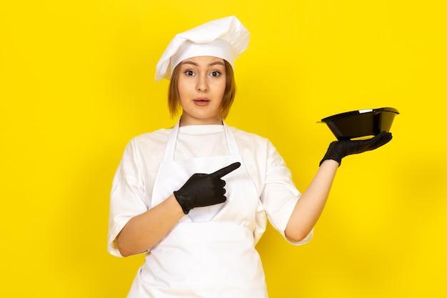 Widok z przodu młoda kobieta kucharka w białym garniturze i białej czapce w czarnych rękawiczkach pokazująca czarną miskę na żółtym tle