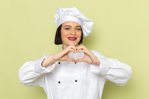 Widok z przodu młoda kobieta kucharka w białym garniturze i czapce pokazująca kształt serca z uśmiechem na zielonej ścianie pani pracuje kolor kuchni żywności