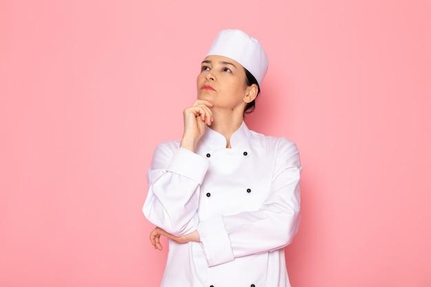 Widok z przodu młoda kobieta kucharz w białym garniturze gotować białą czapkę pozowanie głębokie myślenie wyrażenie
