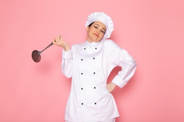 Widok z przodu młoda kobieta kucharz w białym garniturze gotować białą czapkę pozowanie gospodarstwa duże srebrne łyżeczki spokojne wyrażenie