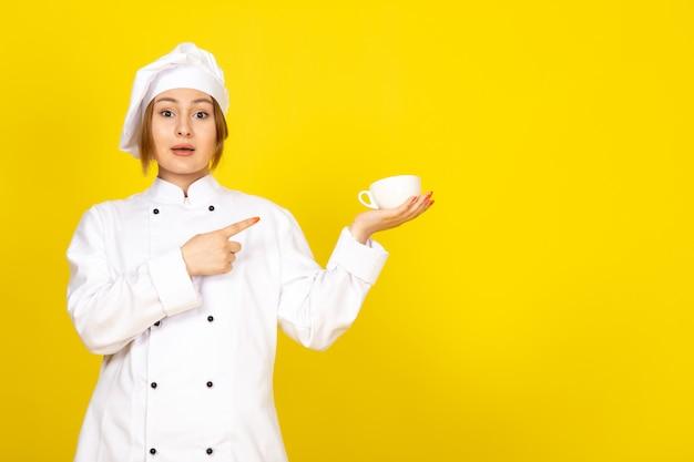 Widok z przodu młoda kobieta kucharz w białym garniturze i białej czapce do picia trzymając filiżankę kawy na żółto
