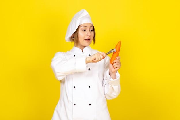 Widok z przodu młoda kobieta kucharz w białym garniturze i białej czapce trzyma i czyści pomarańczową marchewkę na żółto