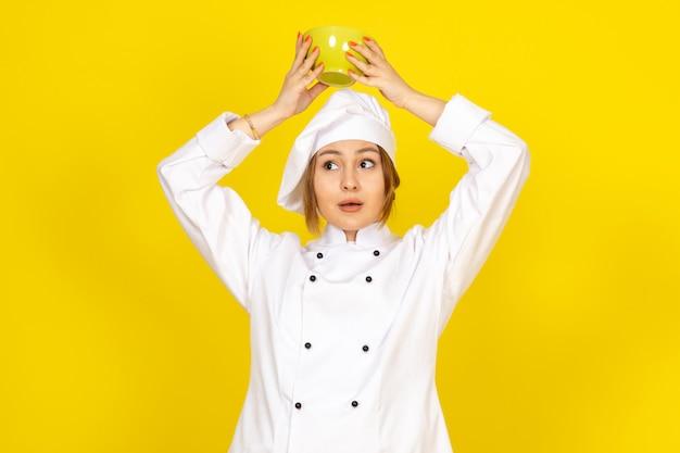 Widok z przodu młoda kobieta kucharz w białym garniturze i białej czapce, trzymając żółty talerz na żółtym
