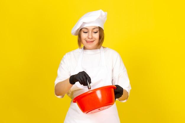 Widok z przodu młoda kobieta kucharz w białym garniturze i białej czapce w czarnych rękawiczkach trzyma czerwoną miskę, mieszając ją na żółto