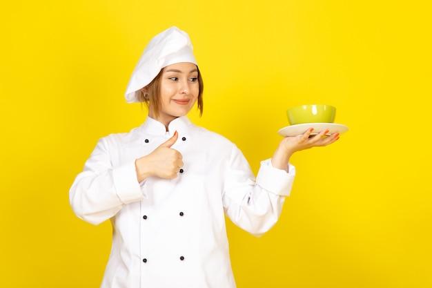 Widok z przodu młoda kobieta kucharz w białym garniturze i białej czapce z żółtymi i czerwonymi talerzami zachwycona, uśmiechając się na żółtym
