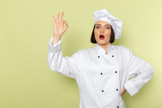 Widok z przodu młoda kobieta kucharz w białym garniturze i czapce pozowanie na zielonej ścianie pani pracuje kolor kuchni żywności