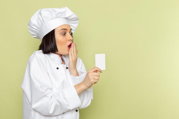 Widok z przodu młoda kobieta kucharz w białym garniturze i czapce trzymającej białą kartę na zielonej ścianie pani pracuje kolor kuchni żywności