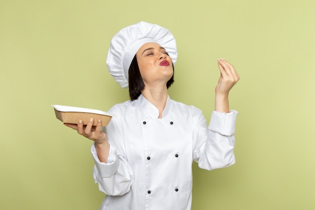 Widok z przodu młoda kobieta kucharz w białym garniturze i czapce trzymającej pakiet z zachwyconym wyrazem na zielonej ścianie pani pracuje kolor kuchni żywności