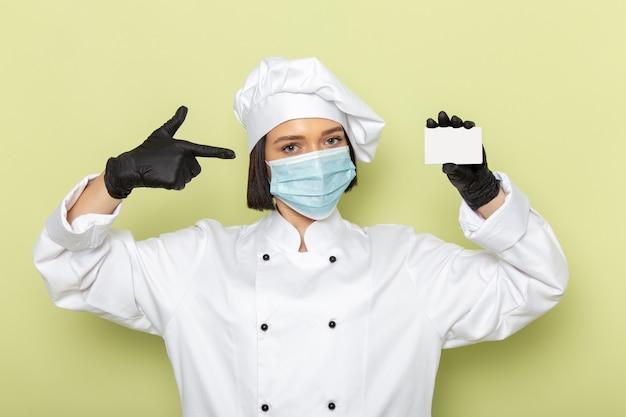 Widok z przodu młoda kobieta kucharz w białym garniturze i czapce w rękawiczkach i masce na zielonej ścianie pani pracuje kolor kuchni żywności