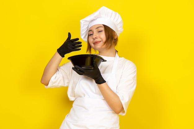 Widok z przodu młoda kobieta kucharz w białym garniturze kucharza i białej czapce w czarnych rękawiczkach trzyma czarną miskę uśmiechając się na żółtym