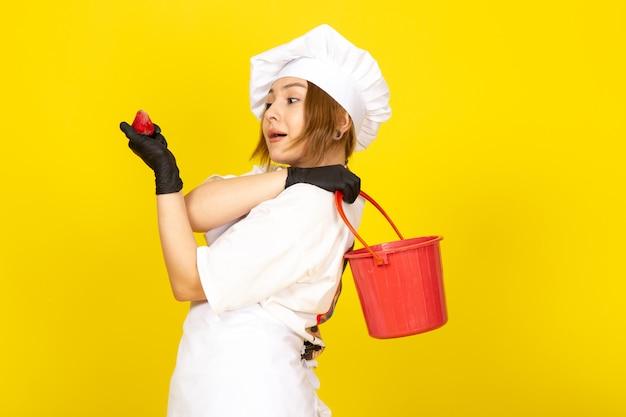 Widok z przodu młoda kobieta kucharz w białym garniturze kucharza i białej czapce w czarnych rękawiczkach, trzymając czerwony kosz i truskawka na żółtym
