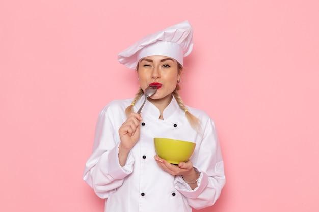 Widok z przodu młoda kobieta kucharz w białym garniturze kucharza pozowanie uśmiechając się i trzymając zielony talerz degustując go na różowej przestrzeni kucharz kuchnia praca praca zdjęcie
