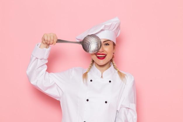 Widok z przodu młoda kobieta kucharz w białym garniturze kucharza pozuje ze srebrną łyżką uśmiechając się na różowym miejscu pracy kucharza kuchni zdjęcie pracy