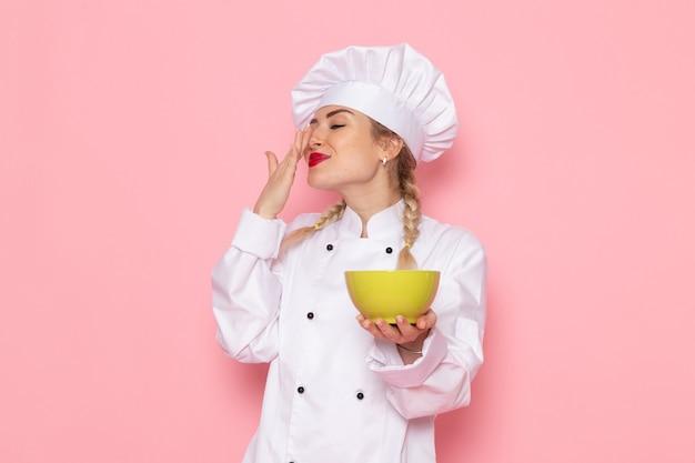 Widok z przodu młoda kobieta kucharz w białym garniturze kucharza, trzymając zielony talerz z uśmiechem na różowej przestrzeni kucharza