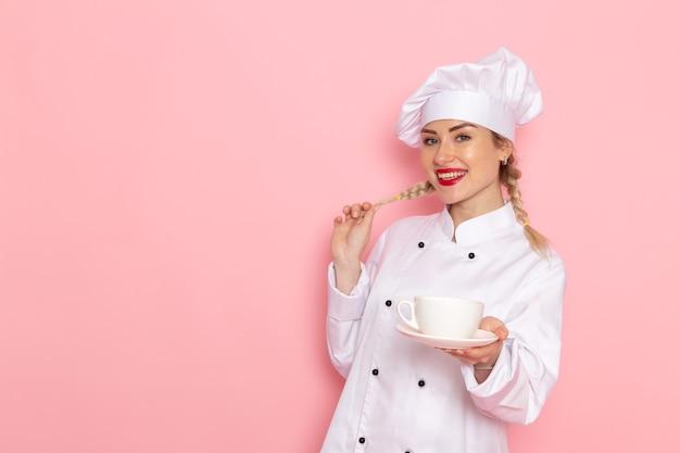 Widok z przodu młoda kobieta kucharz w białym garniturze, trzymając kubek z herbatą na różowym zdjęciu kucharza przestrzeni