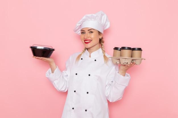 Widok z przodu młoda kobieta kucharz w białym garniturze, trzymając plastikowe filiżanki do kawy i miskę z jedzeniem na różowym kucharzu przestrzeni