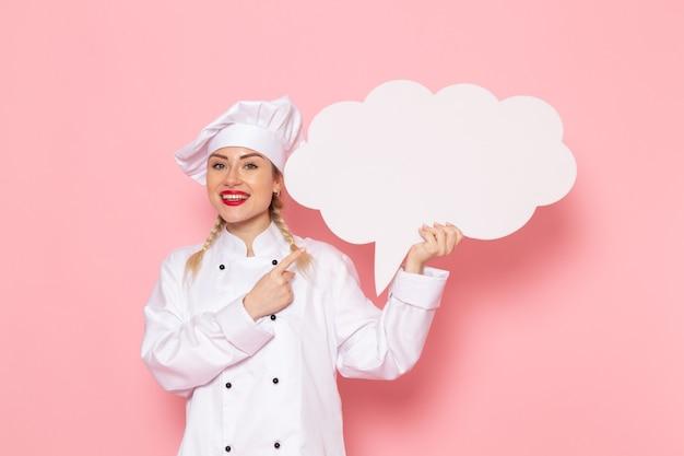Widok z przodu młoda kobieta kucharz w białym garniturze z białym znakiem na różowym zdjęciu kucharza przestrzeni