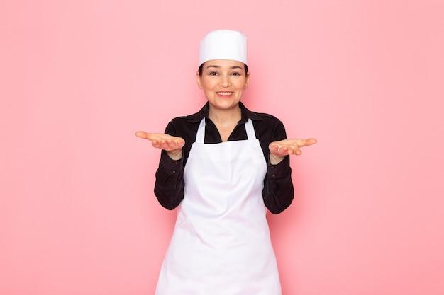 Widok z przodu młoda kobieta kucharz w czarnej koszuli biała kucharz peleryna biała czapka pozowanie pół uśmiech zachwycony uśmiech
