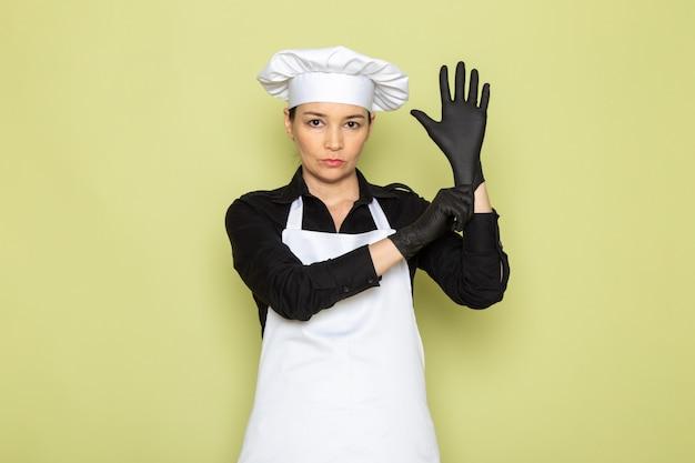Widok z przodu młoda kobieta kucharz w czarnej koszuli biały kucharz peleryna biała czapka pozowanie czarne rękawiczki pozowanie