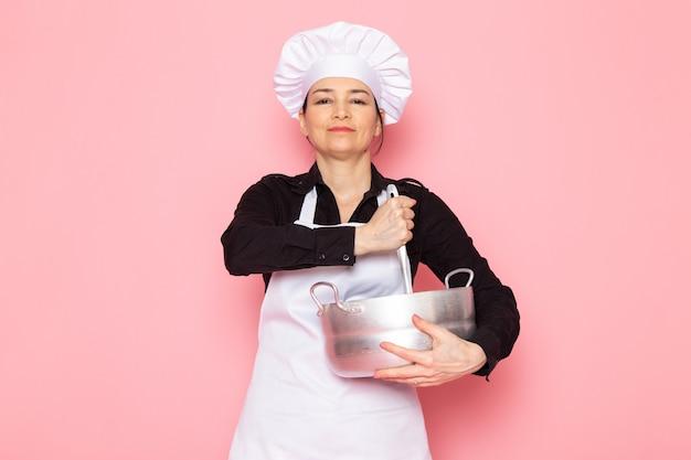 Widok z przodu młoda kobieta kucharz w czarnej koszuli biały kucharz peleryna biała czapka pozowanie gospodarstwa mieszanie srebrny rondel uśmiecha się