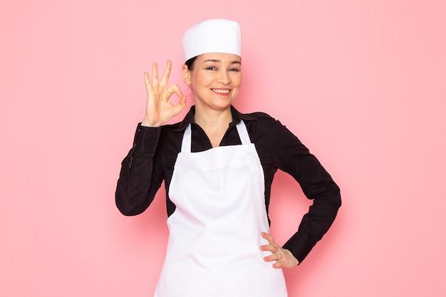 Widok z przodu młoda kobieta kucharz w czarnej koszuli biały kucharz peleryna biała czapka pozowanie uśmiechnięty zachwycony