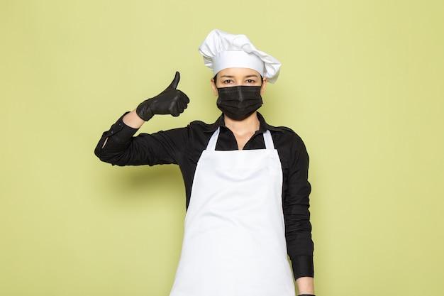 Widok z przodu młoda kobieta kucharz w czarnej koszuli biały kucharz peleryna biała czapka pozowanie w czarne rękawiczki czarne maski pozowanie