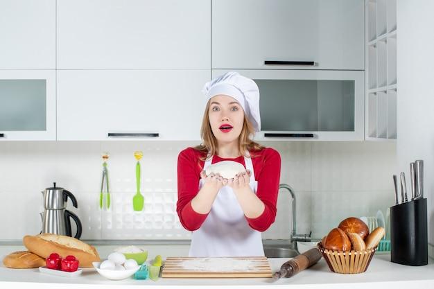 Widok z przodu młoda kobieta kucharz w kapeluszu kucharza i fartuchu, trzymając ciasto