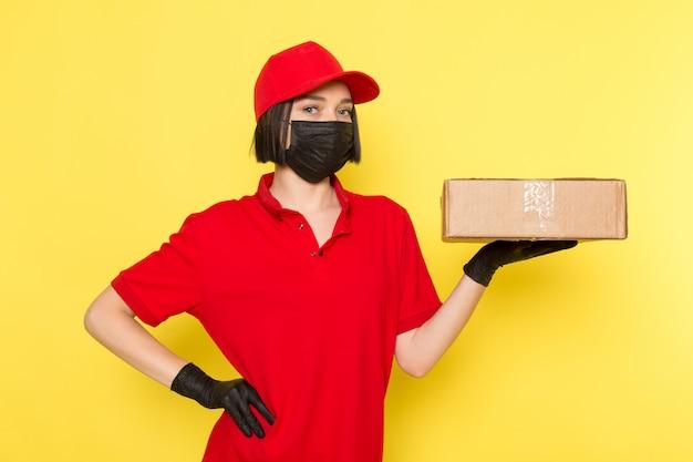 Widok z przodu młoda kobieta kurier w czerwone jednolite czarne rękawiczki i czerwona czapka trzyma pudełko na żywność