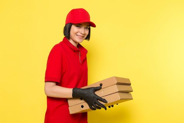 Widok z przodu młoda kobieta kurier w czerwone jednolite czarne rękawiczki i czerwoną czapkę trzyma pudełka z żywnością