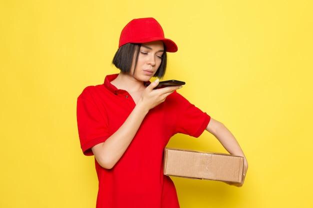 Widok z przodu młoda kobieta kurier w czerwone jednolite czarne rękawiczki i czerwoną czapkę trzyma pudełko z jedzeniem i rozmawia przez telefon